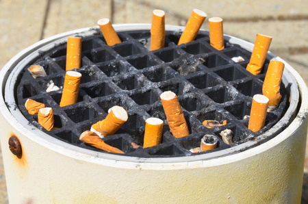 disposed: Close up Smoked Cigarette stubs disposed in dirty, filthy outdoor ashtray, sticking out filter. Stock Photo