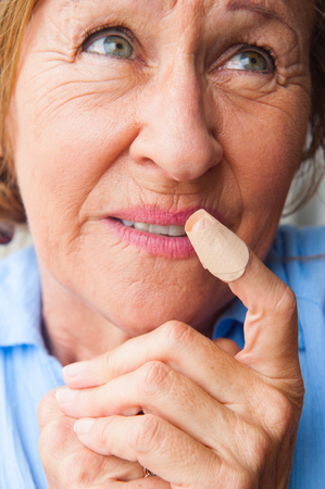 Portrait mature woman in pain, hurt and suffering, close up of plaster on injured, cut bloody finger wound.