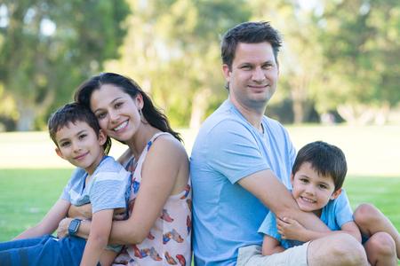 Familia caucásica hispánica interracial feliz del retrato, diversión junto en parque al aire libre, fondo borroso.