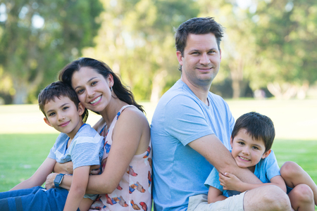 Portrait happy interracial hispanic caucasian family, fun together in park outdoors, blurred background.