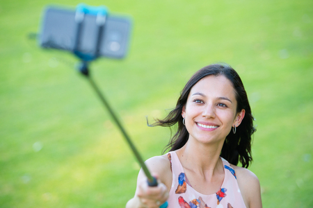 comunication: Portrait Young joyful attractive hispanic woman holding monopod with smart phone taking selfie stick photo outdoor, green blurred background.
