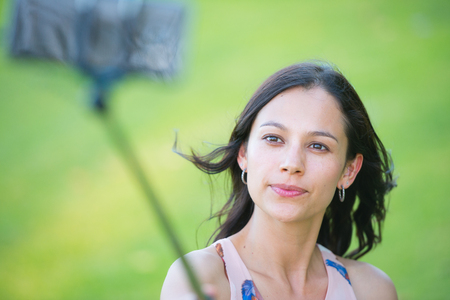 comunication: Portrait Young attractive woman holding monopod with smart phone taking selfie stick photo outdoor, green blurred background. Stock Photo