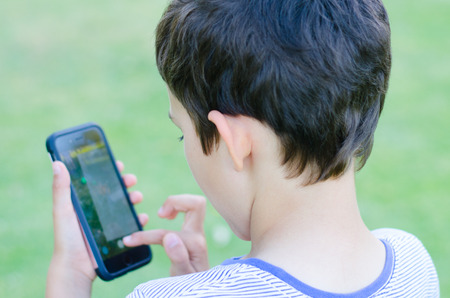 celphone: Back Portrait  young boy playing alone on smartphone in blurred background, internet and social media addiction concept. Stock Photo