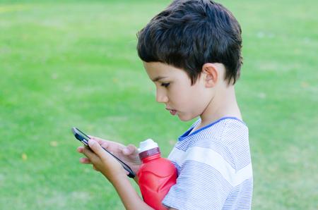 Retrato muchacho joven que usa juegos de teléfonos inteligentes y la interacción social media moderno al aire libre, copia espacio.