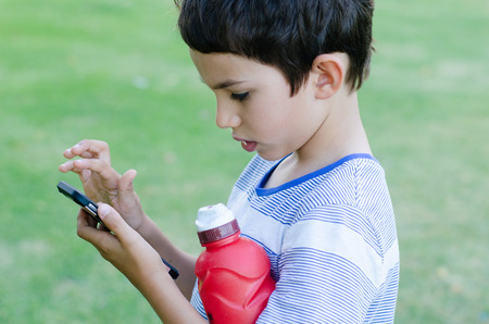 celphone: Portrait young boy using smartphone games and modern social media interaction outdoor. Stock Photo