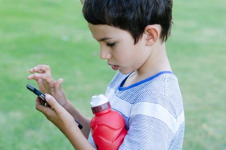Retrato muchacho joven que usa juegos de teléfonos inteligentes y las redes sociales la interacción moderna al aire libre.