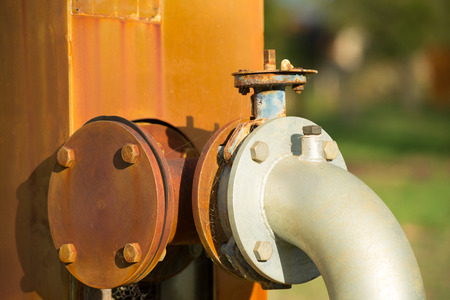 regulating: Close up rustic colored pump pipeline with elbow pipe and old valve for residential energy supply, blurred background and copy space. Stock Photo