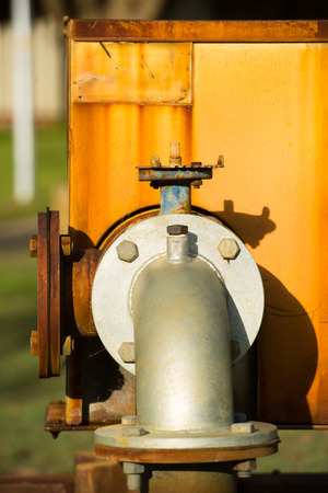 regulating: Close up rustic colored pump pipeline with elbow pipe and old valve for residential energy supply, blurred background. Stock Photo