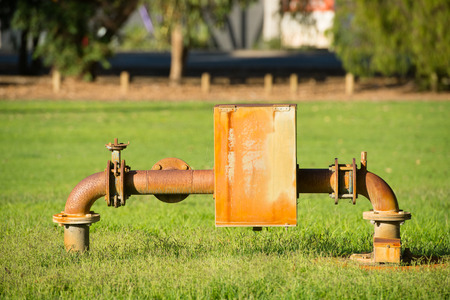Close up rustic colored pump pipeline with elbow pipe and old valve for residential energy supply, blurred background of park and copy space.