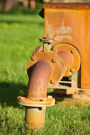 regulating: Close up rustic colored pump pipeline on grass with elbow pipe and old valve for residential energy supply, blurred background and copy space. Stock Photo