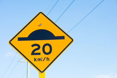 Street sign with speed bump symbol black on yellow and slow down Warning for road traffic, powerline and blue sky background, copy space.