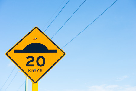 road traffic: Street sign with speed bump symbol black on yellow and slow down area for road traffic, powerline and blue sky background, copy space.