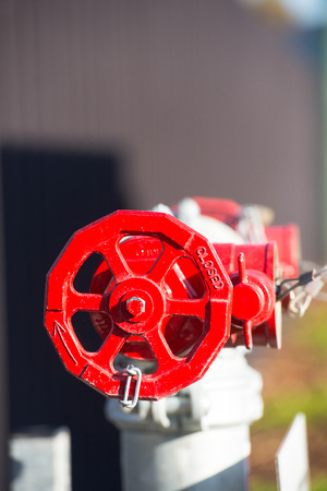 regulating: Industrial red valve and siwtch on pipeline pump, regulating and controlling transport, of energy resources like gas or petrol as well as water, blurred background.