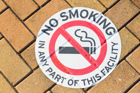 crossed cigarette: No smoking warning symbol or information sign on ground outdoor, with red crossed cigarette on white, textured brick background and copy space.