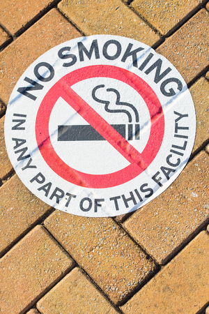 crossed cigarette: No smoking warning symbol or information sign on public ground outdoor, with red crossed cigarette on white, textured brick background and copy space. Stock Photo