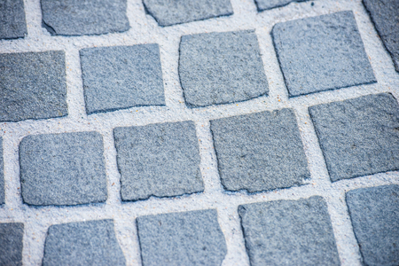 rough road: Close up Detail of path, walkway or street and road with rough square cobble stone pavement as textured backdrop or pattern design background, copy space.