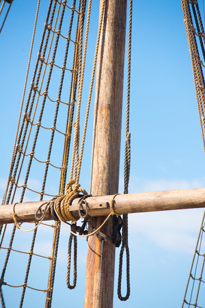 Detail of mast of historic timber sailing ship, with rigging and ropes, blue sky and copy space.