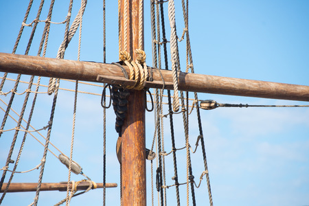 Detail of mast of old ancient historic wooden sailing ship, with rigging and ropes, blue sky and copy space. Stock Photo