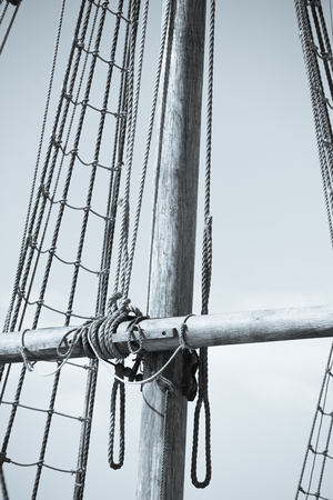 vintage timber: Vintage filtered image of mast of historic timber sailing ship, with rigging and ropes, sky and copy space.
