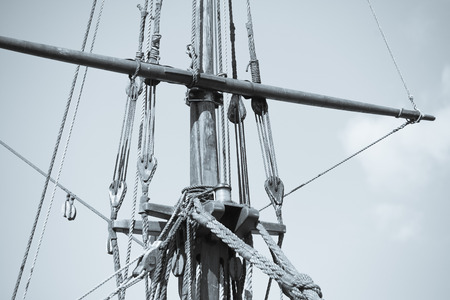 vintage timber: Vintage filtered image  of mast of ancient historic timber sailing vessel, with rigging and ropes, sky and copy space.