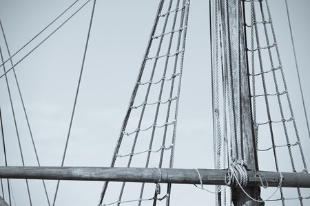 Vintage filtered image  of mast of historic wooden sailing ship, with rigging and ropes, sky and copy space. Imagens