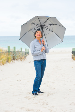 storm background: Portrait attractive mature woman happy, relaxed and friendly with umbrella at beach on cold overcast day, storm clouds over ocean, blurred background, copy space.