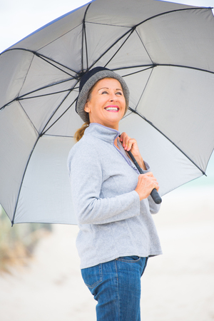 storm background: Close up Portrait attractive mature woman happy, relaxed with umbrella at beach on cold overcast day, storm clouds over ocean, blurred background, copy space.