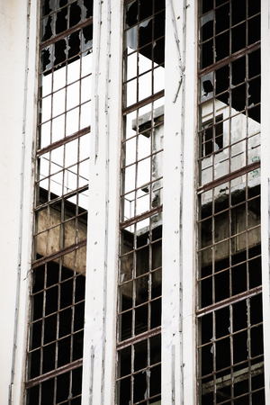 window graffiti: Bleach filtered Exterior view of rundown dirty old abandoned vandalised industrial ruin, broken window glass, rusty steel structure, copy space.