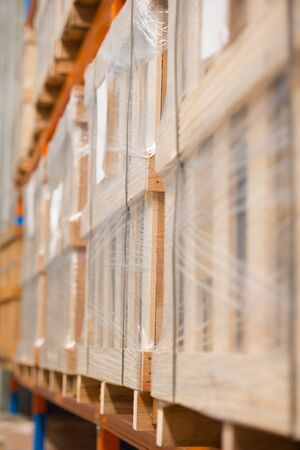 Blurred background of rows of shelves with boxes retail goods in factory warehouse, copy space.