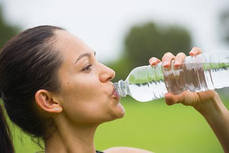Portrait confiant active séduisante jeune femme hispanique active l'eau potable au cours de l'entraînement en plein air, espace de copie et l'arrière-plan flou