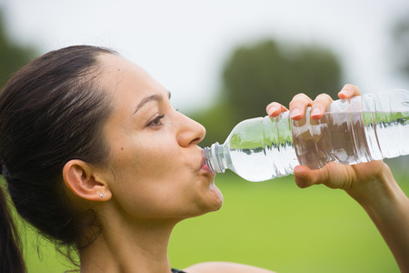 Portrait confident active attractive young hispanic woman drinking water during exercise training outdoor, copy space and blurred background.