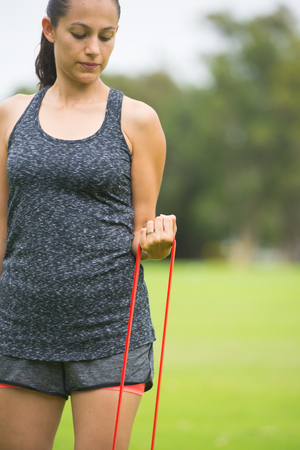 elastic band: Portrait fit active young attractive woman exercising outdoor with red elastic resistance fitness band, stretching arms and legs muscles, blurred background.