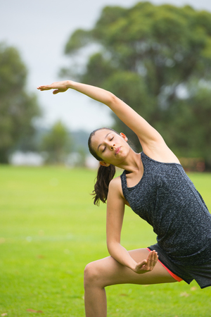 Portrait sporty fit attractive young woman relaxed training yoga or aerobic exercises in park, closed eyes, blurred background outdoor.