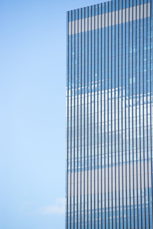 sky reflection: Textured facade of modern design skyscraper office buildings in city business district, reflection in window surface pattern background, blue sky and copy space.