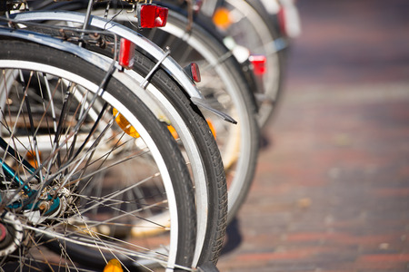 Close up of rear wheels of bicycles parked in a row in the city, blurred background and copy space.