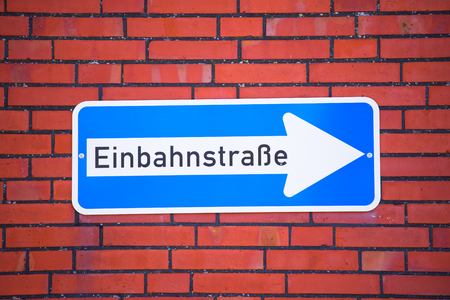 One Way Traffic Sign in German with white right pointing arrow on blue, German text information, red brick wall as background and copy space. Stock Photo