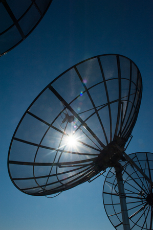 Satellite dishes against blue sky and sun back lit, for modern wireless communication and data transmission, copy space. Stock Photo