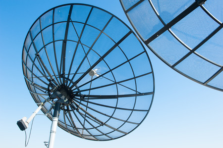 Satellite dishes against blue sky, for modern wireless communication and data transmission, copy space.