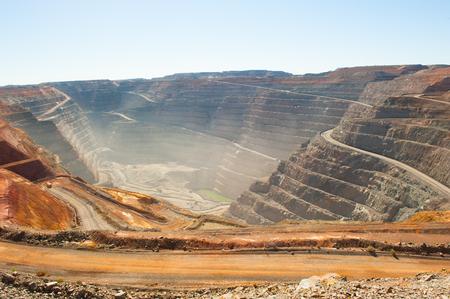 Panoramische luchtmening van Super Pit-goudmijn in Kalgoorlie, Westelijk Australië, met windende weg langs randen van de gehele, zware machines, de zomer zonnige stoffige blauwe hemel.