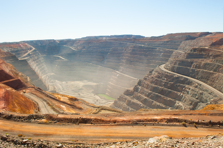 Panoramic aerial view of Super Pit goldmine in Kalgoorlie, Western Australia, with winding path along edges of the whole, heavy machinery, summer sunny dusty blue sky.
