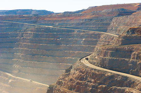 Panoramic aerial view of Super Pit goldmine in Kalgoorlie, Western Australia, with trucks on winding path along edges of the whole, heavy machinery, summer sunny dusty blue sky. Imagens