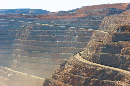 Panoramische luchtmening van Super Pit-goudmijn in Kalgoorlie, Westelijk Australië, met vrachtwagens op windend weg langs randen van de gehele, zware machines, de zomer zonnige stoffige blauwe hemel. Stockfoto - 80077116