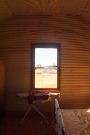 Old grunge dirty bedroom in abandoned farm house ruin in remote Australia, with bed, ironboard, wardrobe, sunshine through window view, copy space.