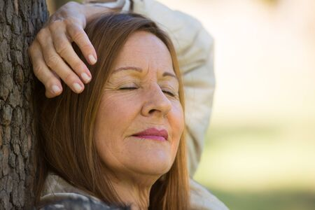 Portrait attractive mature woman relaxed in park with closed eyes, peaceful daydreaming, contemplating, thoughtful, blurred background. Stock Photo