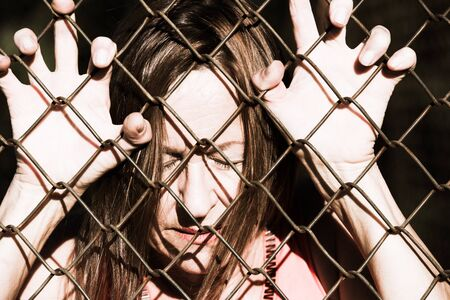 jail: Filtered image Portrait of devastated, stressed mature woman with closed eyes and hands gripped on behind mesh wire fence