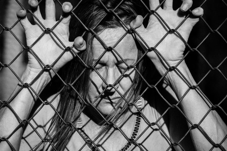 wire mesh: Filtered image Portrait of devastated, stressed mature woman with closed eyes and hands gripped on behind mesh wire fence