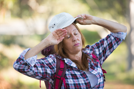 Portrait active attractive mature woman exhausted and tired of walking and hiking with backpack in the woods, blurred background. Stock Photo
