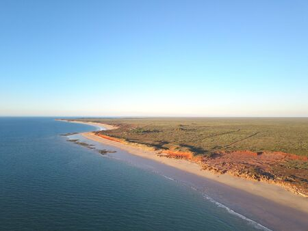 Scenic aerial panoramic view of remote coast near Broome, Western Australia, with ocean, beach, red cliffs, outback landscape and sunny blue sky as copy space Banco de Imagens
