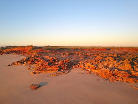 Scenic aerial panoramic view of remote coast near Broome, Western Australia, with ocean beach, red cliffs, outback landscape and sunset blue sky as copy space.