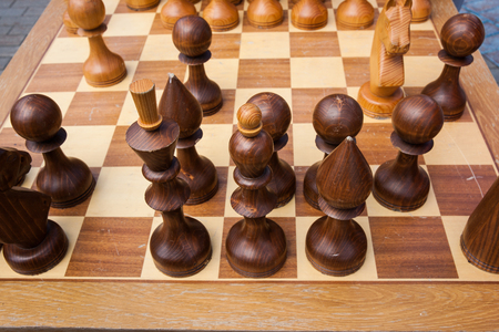 Brown wooden chess pieces on a chess board. The game is under way. Open air chess competitions. Nobody around